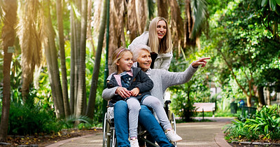 Buy stock photo Cropped shot of a cheerful elderly woman in a wheelchair spending time with her daughter and grandchild outside in a park