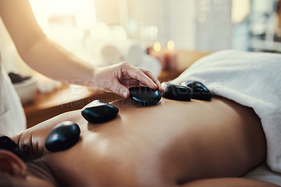 Buy stock photo Closeup shot of a woman getting a hot stone massage at a spa