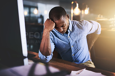 Buy stock photo Cropped shot of a handsome young businessman suffering from backache while working at his desk during a late night at work