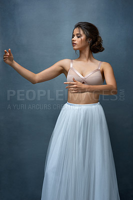 Buy stock photo Studio shot of an attractive young female ballet dancer posing against a grey background