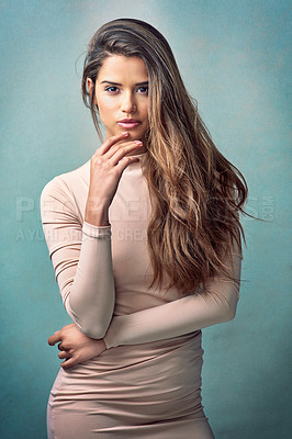 Buy stock photo Studio portrait of an attractive young woman posing against a green background
