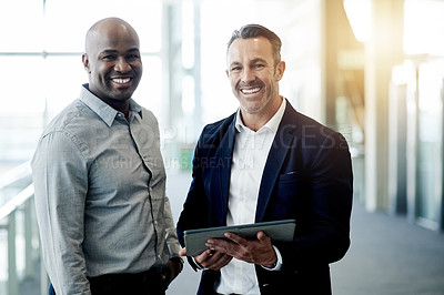 Buy stock photo Cropped portrait of two handsome businessmen looking at a tablet in their corporate office