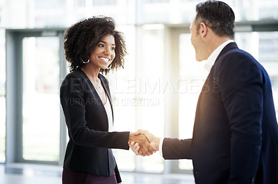 Buy stock photo Cropped shot of a businessman and businesswoman shaking hands in their corporate office