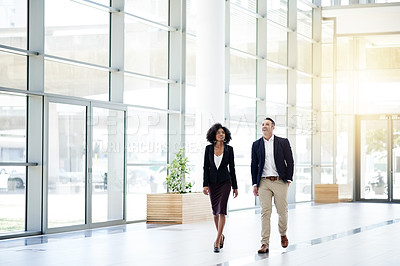 Buy stock photo Full length shot of two business colleagues walking through their corporate office