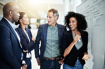Buy stock photo Cropped shot of a group of businesspeople strategizing on a whiteboard in their corporate office