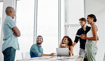 Buy stock photo Shot of a group of young businesspeople having a meeting around a table in an office