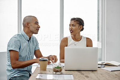 Buy stock photo Shot of two young businesspeople sitting around a table and using a laptop in an office