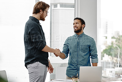 Buy stock photo Shot of two young businessmen shaking hands inside of an office