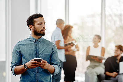 Buy stock photo Shot of a young businessman using his cellphone in an office with his colleagues in the background