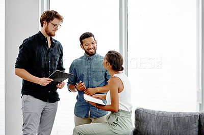 Buy stock photo Shot of three young businesspeople having a discussion in their office