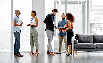 Buy stock photo Full length shot of a group of young businesspeople standing and having discussions in their office