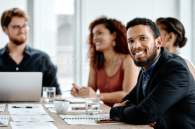 Buy stock photo Portrait of a cheerful young businessman sitting around a table with colleagues at work