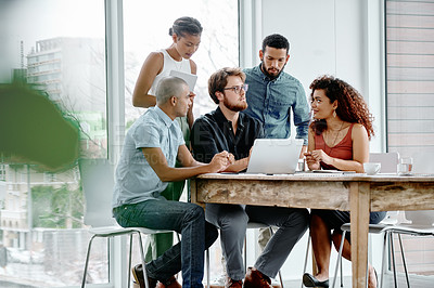 Buy stock photo Full length shot of a group of young businesspeople working on a laptop together in their office