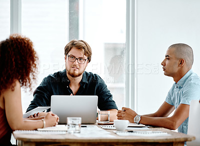 Buy stock photo Shot of three young businesspeople having a meeting around a table in an office