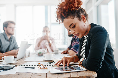 Buy stock photo Shot of a young businesswoman using a laptop during a meeting in a modern office