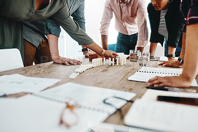 Buy stock photo Shot of a group of young businesspeople having a meeting with dominoes in a modern office