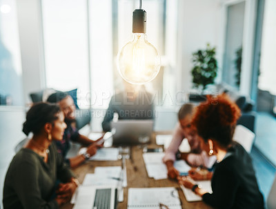 Buy stock photo Shot of a group of young businesspeople having a meeting with a lightbulb in the foreground