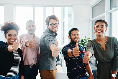 Buy stock photo Shot of a group of young businesspeople showing thumbs up in a modern officeShot of a group of young businesspeople showing thumbs up in a modern office