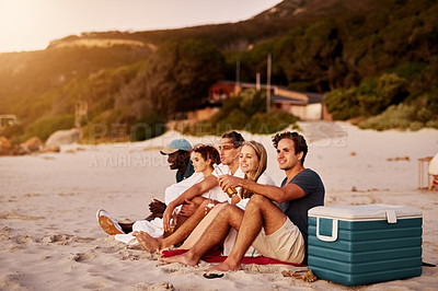 Buy stock photo Shot of a group of friends sitting together on the beach
