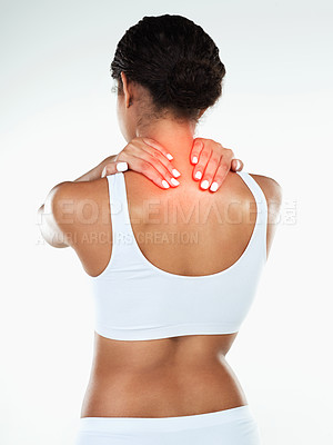 Buy stock photo Rearview studio shot of an unrecognizable woman holding her neck due to pain while standing against a white background