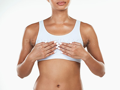 Buy stock photo Studio shot of an unrecognizable woman holding her chest while standing against a white background