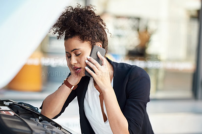 Buy stock photo Cropped shot of a frustrated young businesswoman calling roadside assistance after her car broke down