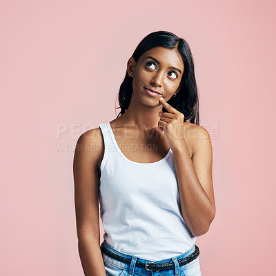 Buy stock photo Studio portrait of a beautiful young woman looking thoughtful against a pink background