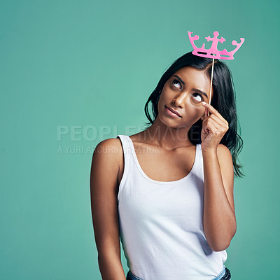 Buy stock photo Studio shot of a beautiful young woman posing with a prop crown against a green background