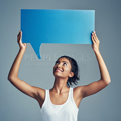 Buy stock photo Studio shot of a beautiful young woman holding up a blank signboard against a grey background