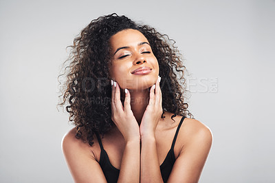 Buy stock photo Studio shot of a beautiful young woman touching her skin against a grey background