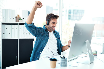 Buy stock photo Shot of a cheerful male call centre agent punching the air in celebration in his office