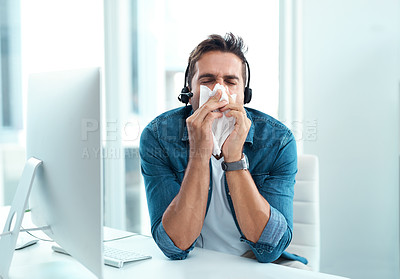 Buy stock photo Shot of a male call centre agent blowing his nose with a tissue in his office