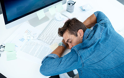 Buy stock photo High angle shot of an exhausted young businessman taking a nap on his desk in his office
