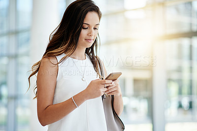 Buy stock photo Cropped shot of a confident young businesswoman talking on her cellphone at work during the day