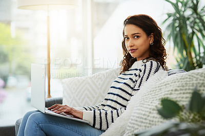 Buy stock photo Portrait of an attractive young woman using her laptop while relaxing on a couch at home
