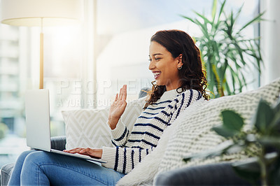 Buy stock photo Shot of a young woman using her laptop to make a video call while relaxing on a couch at home