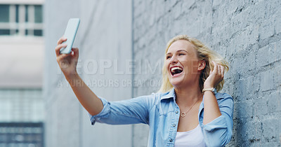 Buy stock photo Shot of a confident young woman taking selfies outdoors