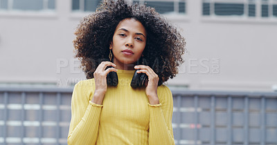 Buy stock photo Portrait of a confident young woman wearing headphones around her neck outdoors