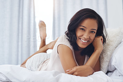 Buy stock photo Shot of a happy young woman waking up in the morning in bed