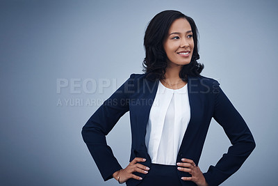 Buy stock photo Studio shot of a young businesswoman standing with her hands on her hips against a grey background