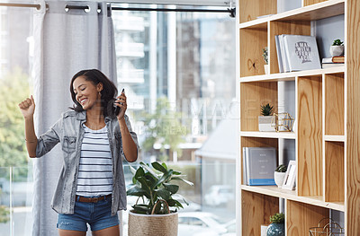 Buy stock photo Shot of a young woman dancing while listening to music from her cellphone at home