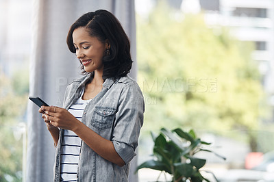 Buy stock photo Shot of a young woman using a cellphone at home