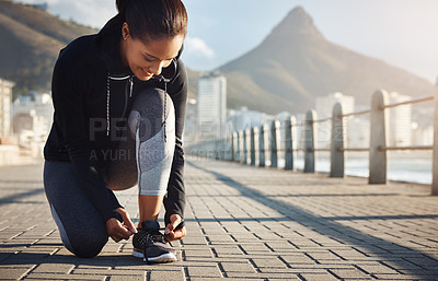 Buy stock photo Shot of a fit young woman tying her shoelaces before going for a run on the promenade