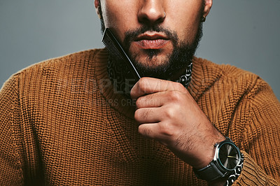 Buy stock photo Cropped studio shot of a young man combing his beard against a grey background