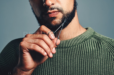 Buy stock photo Cropped studio shot of a young man trimming his beard against a grey background