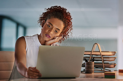Buy stock photo Shot of a young businesswoman working on her laptop during a late night in the office