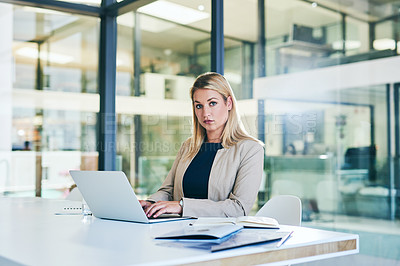Buy stock photo Cropped portrait of an attractive young businesswoman working on a laptop in her corporate office