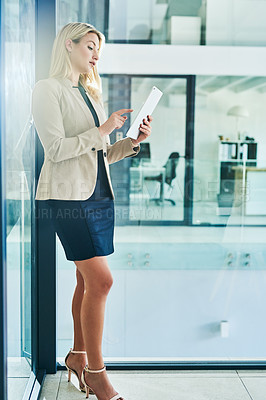 Buy stock photo Cropped shot of an attractive young businesswoman working on a tablet in her corporate office