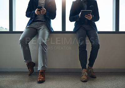 Buy stock photo Cropped shot of two businessmen using a digital tablet and cellphone while leaning against a wall in a modern office