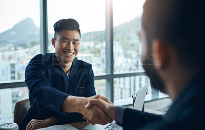 Buy stock photo Shot of two young businessmen shaking hands while sitting at a desk in a modern office